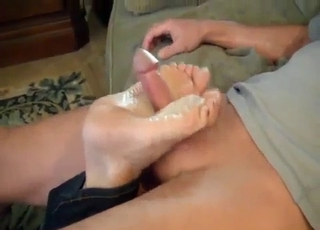 Redhead sister gives her brother a nice footjob